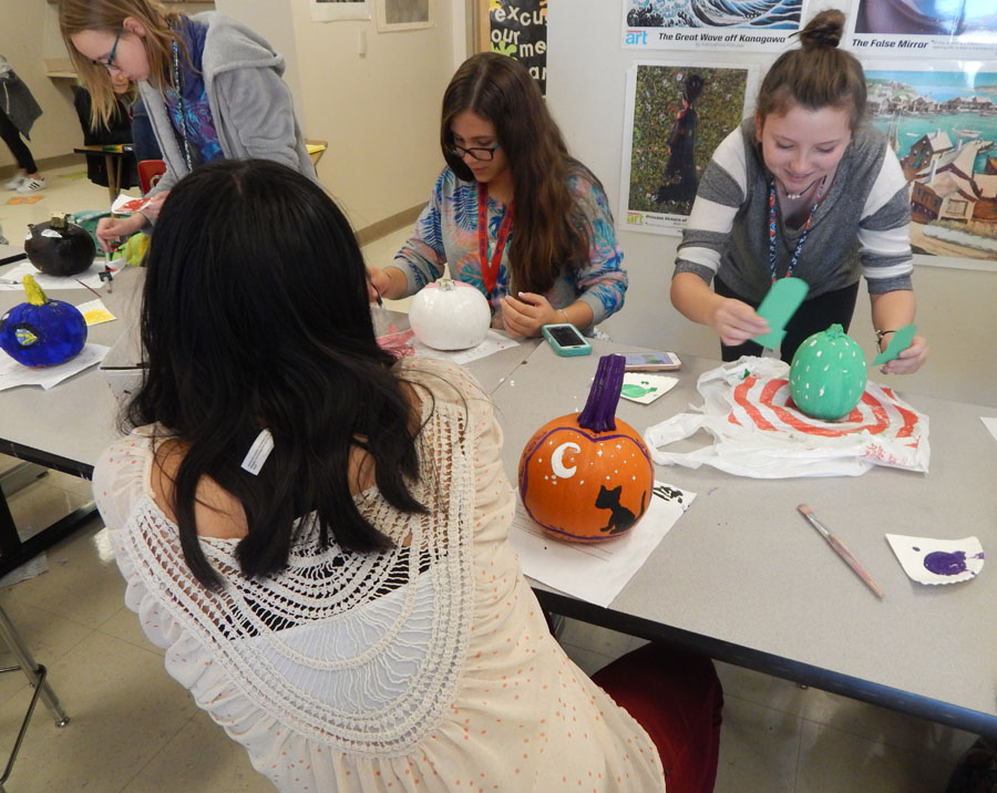 Art Club members paint pumpkins